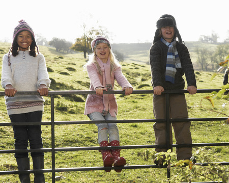 leaning by barrier: Children swinging on gate in countryside