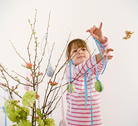 girl decorating twigs for easter
