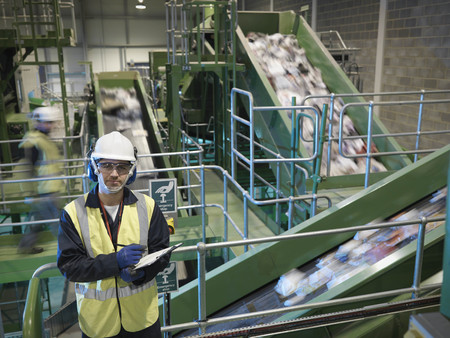Worker With Notes In Recycle Plant LANG_EVOIMAGES