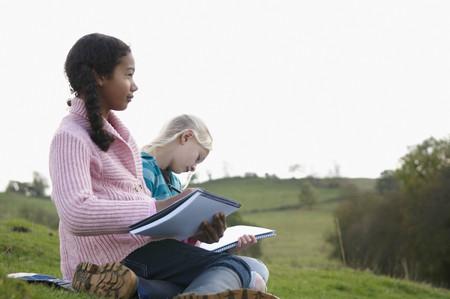 held down: Two girls sketching on hillside