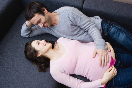 advances: Pregnant woman and man laying on couch