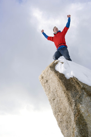 climber celebrating on snow capped peak LANG_EVOIMAGES