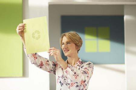 accountable: Woman looking at recycling logo