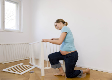 knelt: Pregnant woman putting together baby bed