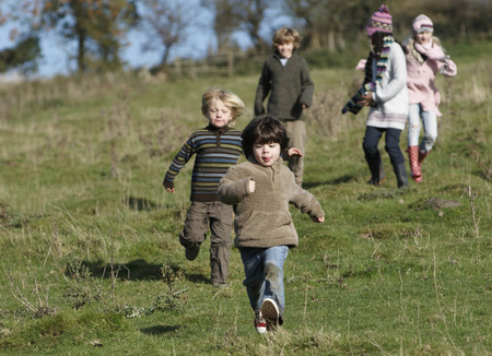 pursuing: Children running in countryside LANG_EVOIMAGES