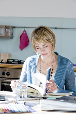 tomes: Woman sitting in kitchen reading
