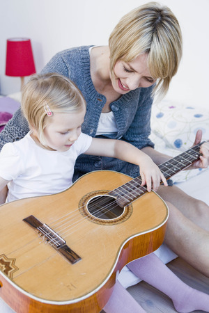 abodes: Girl and woman playing with a guitar