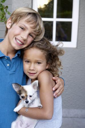 curare teneramente: Fratello e sorella con il loro cane