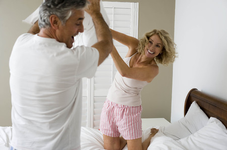 mischeif: Man and woman pillow fighting