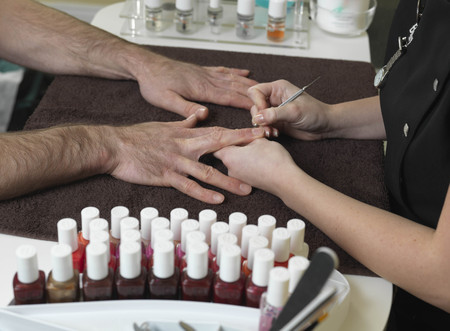 women s health: male hands receiving manicure LANG_EVOIMAGES