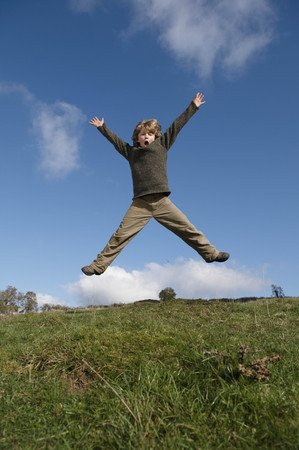 Boy jumping on hill LANG_EVOIMAGES