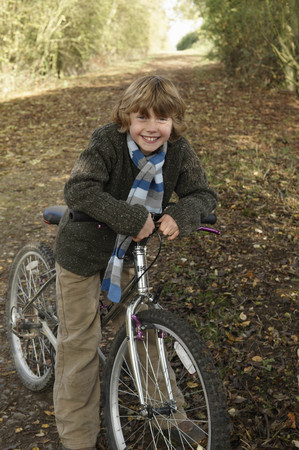 road autumnal: Boy with bike on country lane LANG_EVOIMAGES