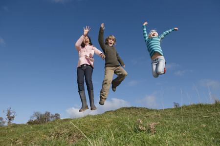 exhilarating: Children jumping on hill LANG_EVOIMAGES