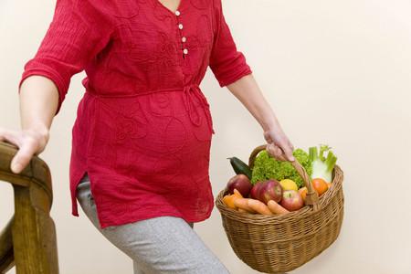 ascends: pregnant woman carrying fruit basket LANG_EVOIMAGES