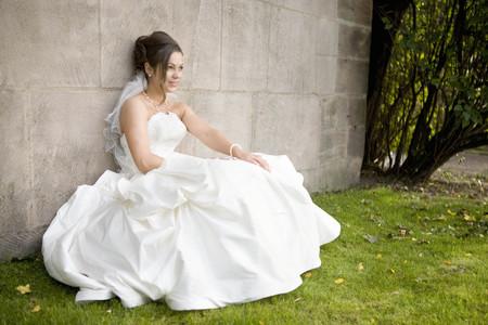 Bride sitting at a wall.