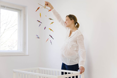 Pregnant woman looking at mobile toy