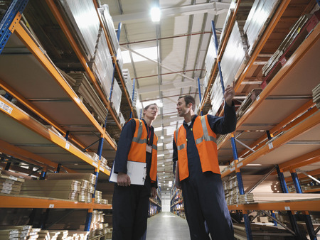 distribution board: Workers Discussing Products In Warehouse