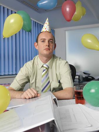 Grumpy office worker in party hat