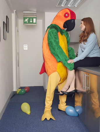 silliness: Man in parrot outfit with co worker LANG_EVOIMAGES