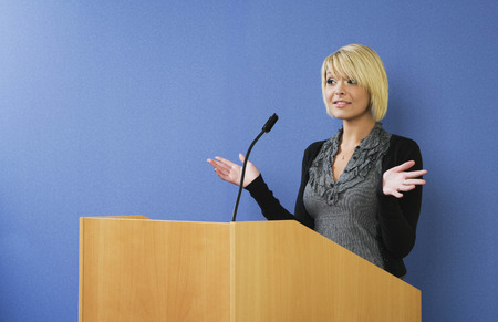 motioning: Woman talking from lectern LANG_EVOIMAGES