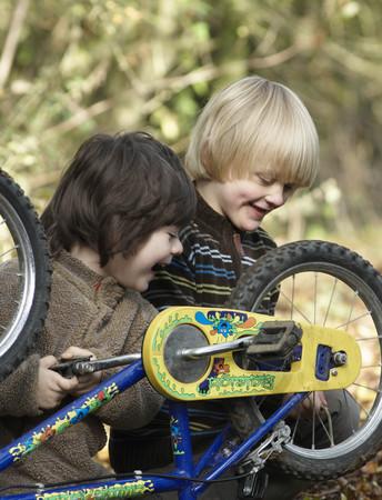 transportation: Two boys examine bikes on country lane
