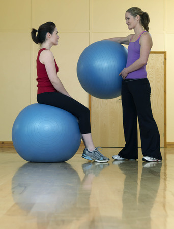 low spirited: women relaxing at gym with exercise ball