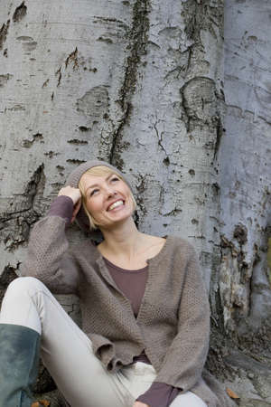 chic woman: Woman leaning at tree laughing