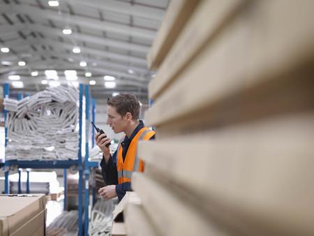 Worker On Walkie Talkie In Warehouse