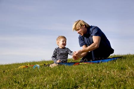 agachado: Niño y padre juntos un Kite