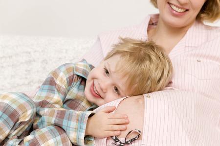 curare teneramente: Donna incinta e ragazzo che ride