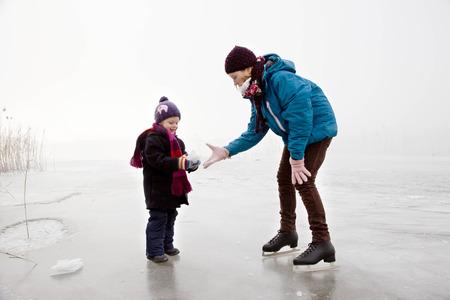 techniek: Meisje en jongen iceskating op bevroren meer