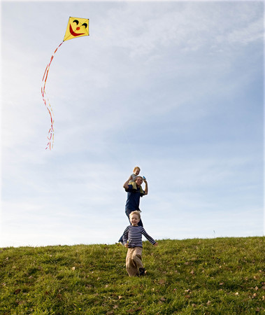 Two Boys and father fly a Kite