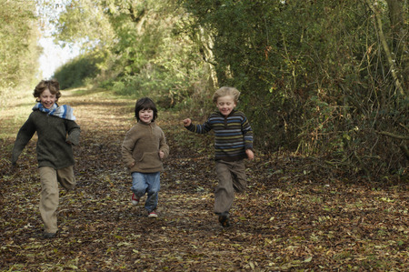 road autumnal: Boys running down country lane LANG_EVOIMAGES