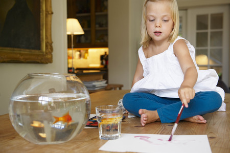 enthusiastically: Girl on table, painting next to goldfish