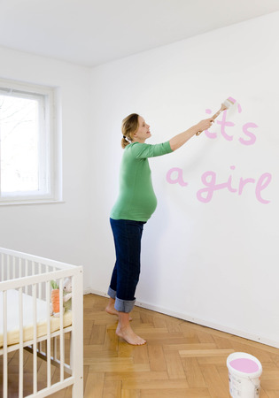 Pregnant woman painting nursery LANG_EVOIMAGES