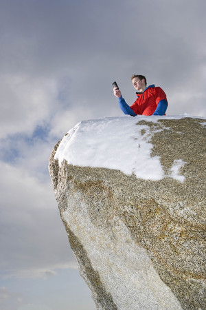 climber taking picture on mountain peak