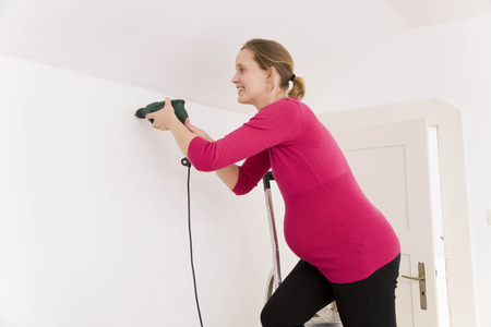 Pregnant woman with power drill