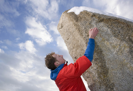 climber free climbing snow capped peak