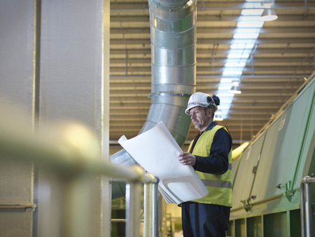protects: Worker With Plans In Plant