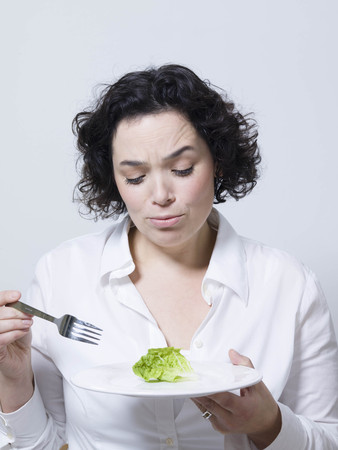 adverse: woman looking at a leaf of salad