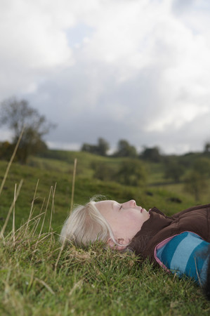 english ethnicity: Girl lying on grass looking at sky