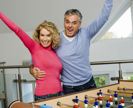 prevailing: Couple having fun playing table football LANG_EVOIMAGES