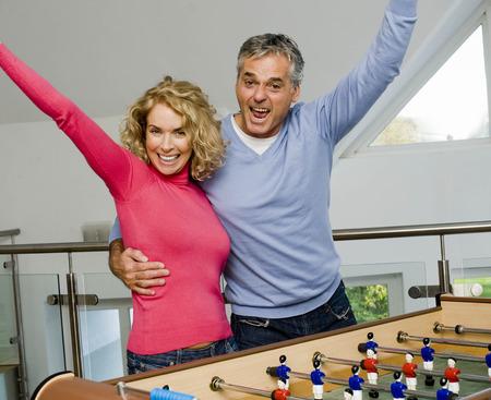 shrieking: Couple having fun playing table football LANG_EVOIMAGES