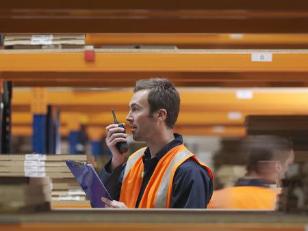 distribution board: Worker On Walkie Talkie In Warehouse