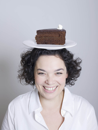 woman with a plate of cake on her head