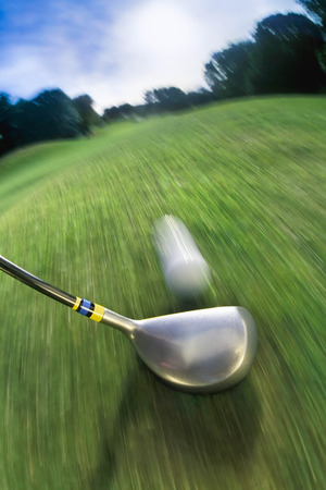 Golf club hitting ball on golf course LANG_EVOIMAGES
