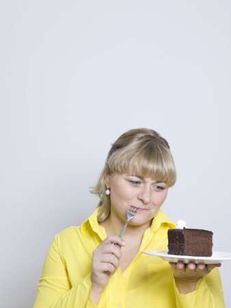 woman looking at plate of cake LANG_EVOIMAGES