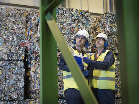 warming up: Recycle Workers With Bales Of Tin Cans