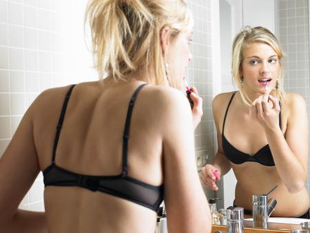 pubescent: Girl applying makeup in bathroom
