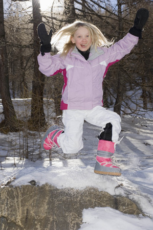 snows: Girl Jumping wearing ski outfit LANG_EVOIMAGES